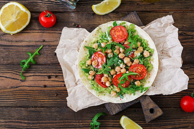 Vegan tacos with guacamole, chickpeas, tomatoes and arugula. healthy food.  top view