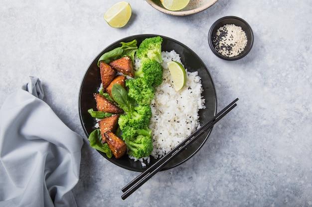 Веганские теряки темпе или темпе будда чаша с рисом, брокколи на пару, шпинат и лайм на сером фоне. здоровая пища