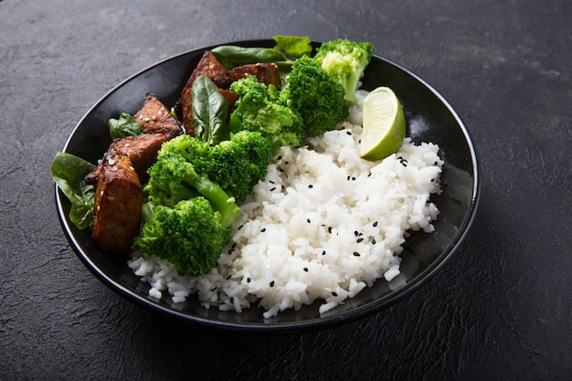Vegan teryaki  tempeh or tempe buddha bowl  with rice, steamed broccoli, spinach  and lime on black  background. healthy food
