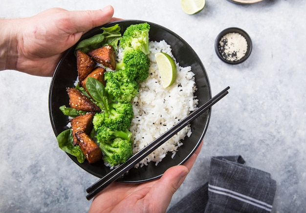 Vegan teryaki  tempeh or tempe buddha bowl  with rice, steamed broccoli, spinach  and lime on gray background. healthy food