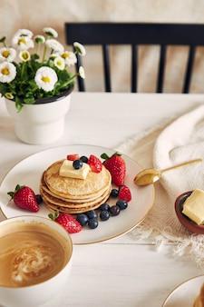 과일과 함께 흰색 접시에 채식주의 두부 팬케이크
