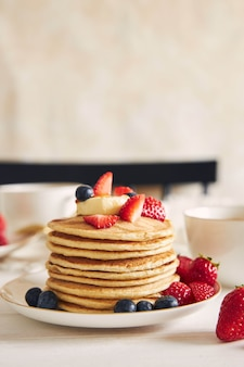 Vegan tofu pancakes with fruits on a white plate