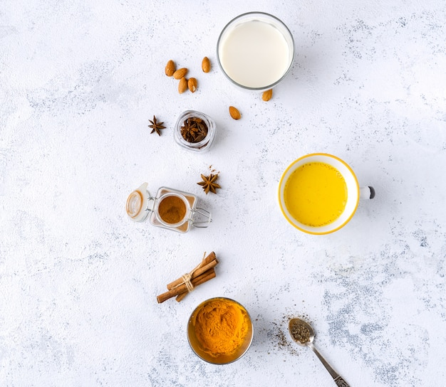 Vegan turmeric latte in a mug, almond milk, spices on white textured table, top view