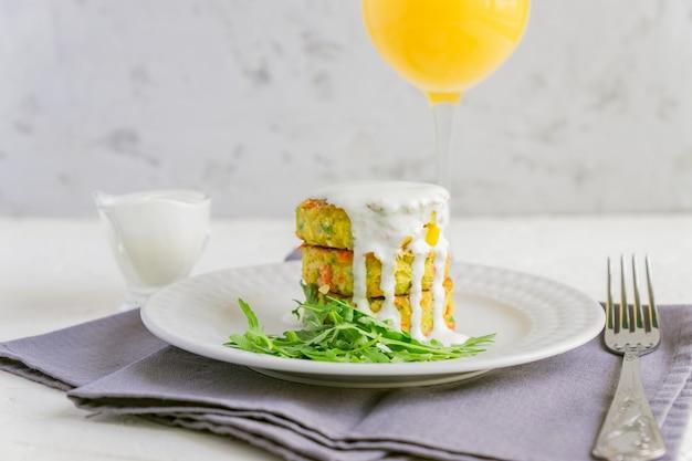 ルッコラサラダとソースのビーガン野菜バーガーを白い皿とオレンジジュースで提供しています