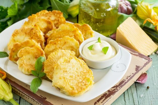 ビーガン野菜のフリッターズッキーニとサワークリームガーリックソース揚げたカツレツまたはパンケーキ