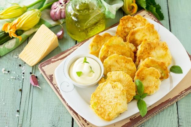 ビーガン野菜のフリッターズッキーニとサワークリームガーリックソースをキッチンの木製テーブルに