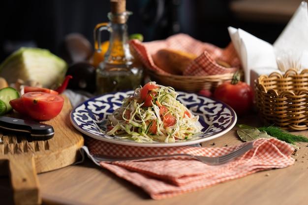 伝統的なウズベキスタンの皿に油で味付けしたキャベツ、キュウリ、トマトのビーガン野菜サラダ