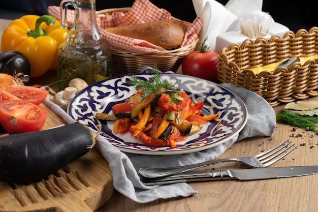 伝統的なウズベキスタンのプレートに油で味付けしたナス、ニンジン、ピーマン、キュウリ、トマトのビーガン野菜サラダ