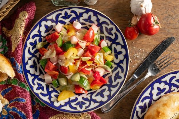 フォークとナイフでカトラリーの横にある木製のテーブルに伝統的なウズベックの装飾が施されたセラミックプレートに、ピーマン、きゅうり、トマト、大根、玉ねぎのビーガン野菜サラダ。上面図