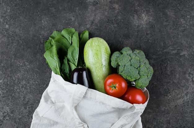Vegan vegetables in cotoon reusable bag on dark slate table. zero waste, care, health concept
