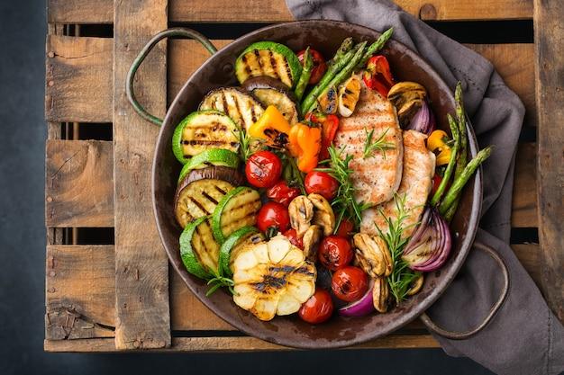 Веганские, вегетарианские, сезонные, летние блюда. жареные овощи в сковороде на темно-черном столе. плоский фон вид сверху