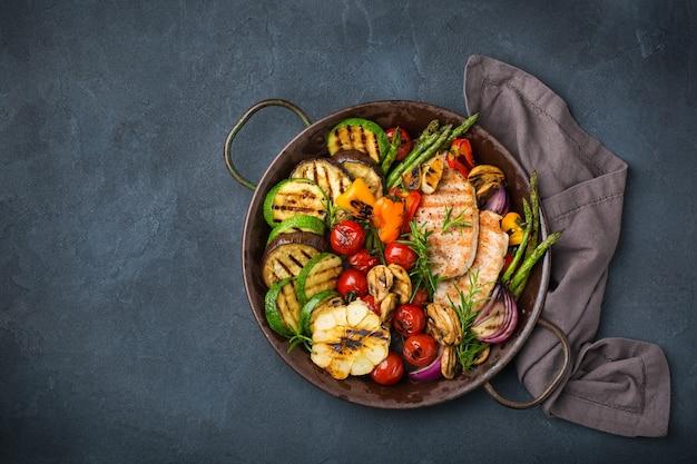 Веганские, вегетарианские, сезонные, летние блюда. жареные овощи в сковороде на темно-черном столе. вид сверху плоская копия космического фона