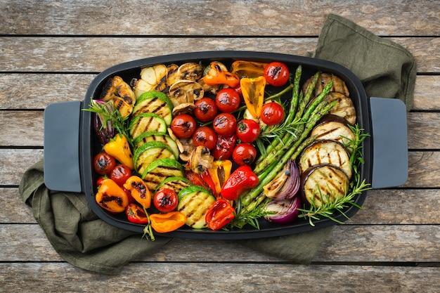 Веганские, вегетарианские, сезонные, летние блюда. жареные овощи в сковороде на деревянном столе. плоский фон вид сверху