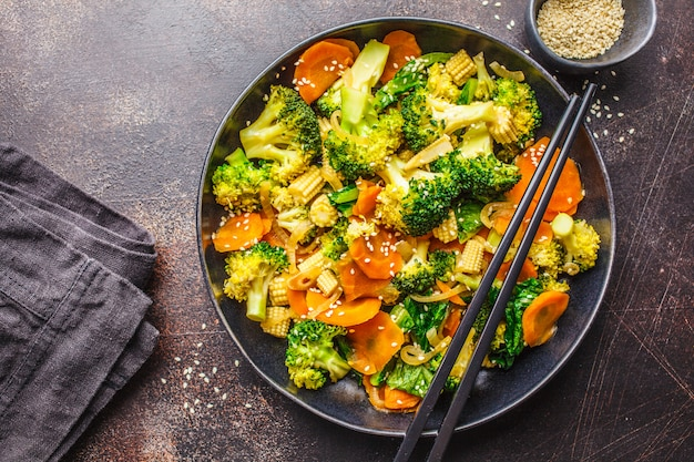 Vegan wok stir fry with broccoli and carrot in black dish, top view, copy space.