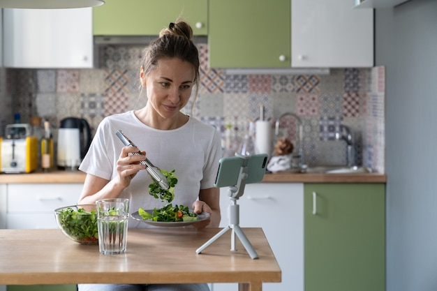 Vegan woman eating healthy salad of fresh herbs and vegetables watching movie on smart phone at home
