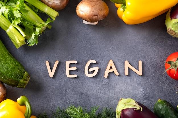 生の有機野菜と灰色の木製の文字で書かれたビーガンの言葉。