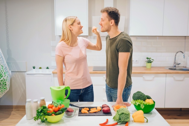 Vegan young woman gives cutting piece of vegetable for her husband