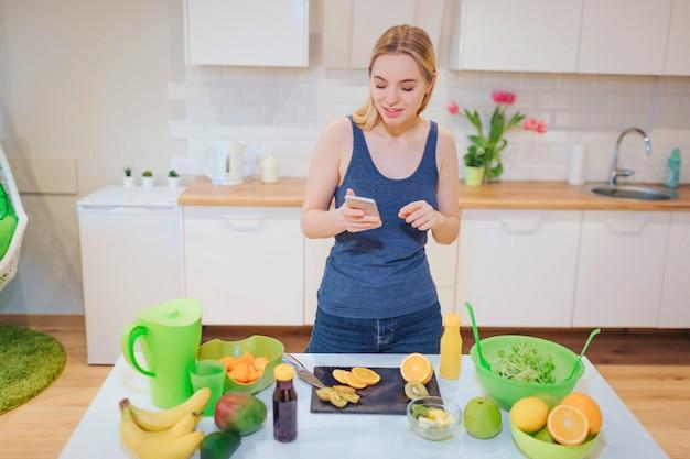 Vegan красивая блондинка с смартфона, фотографирование органического апельсина на кухне