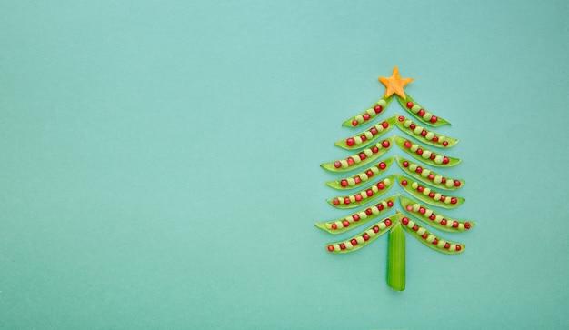 ミントの背景にグリーンピースで作られたビーガンのクリスマスツリー