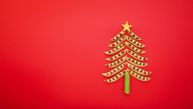 赤い背景に緑のエンドウ豆で作られたビーガンのクリスマスツリー