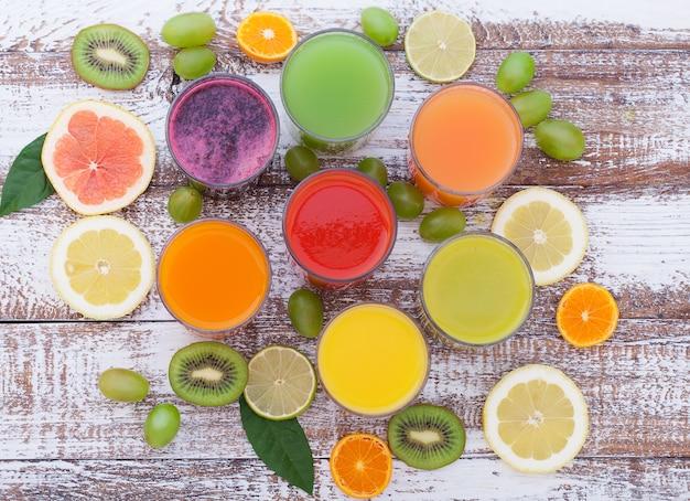 Соки овощные и цитрусовые. кусочки овощей и фруктов на деревянном столе. необычный вид сверху