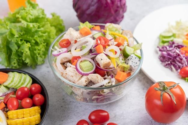 Овощной и фруктовый салат на белом фоне.