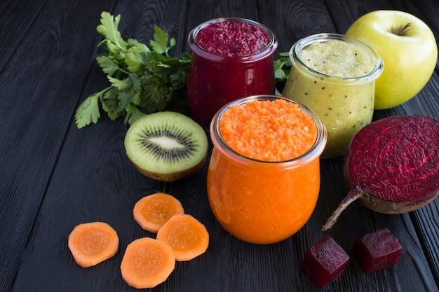 小さなガラスの瓶に入った野菜と果物のスムージー