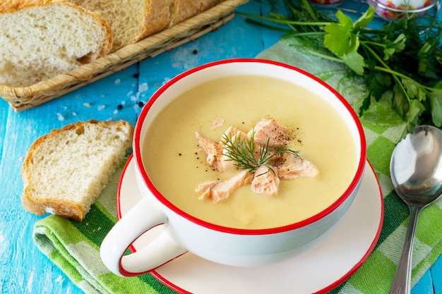 キッチンの木製の背景にクリームとパセリと野菜と赤の魚のスープ