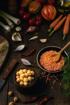 Vegetable assortment, lentils, chickpeas on brown wooden table, top view