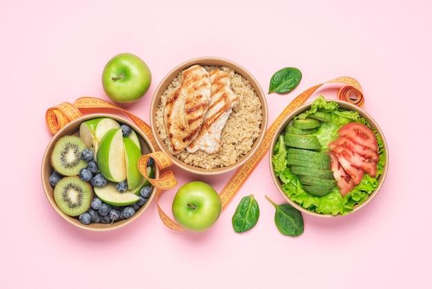Овощной салат из авокадо, киноа с куриной грудкой, фруктами и ягодами на розовом фоне