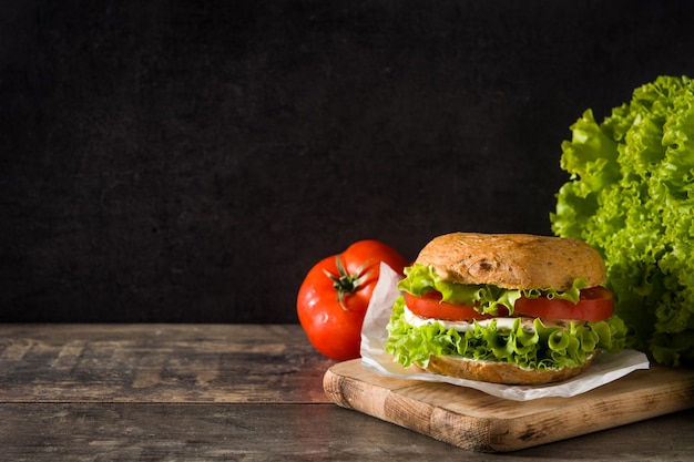Vegetable bagel sandwich with tomato, lettuce, and mozzarella cheese on wooden table copy space
