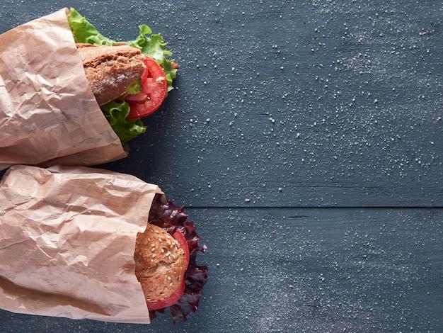 野菜のバゲットサンドイッチ、紙袋、木製の背景、コピースペース付き