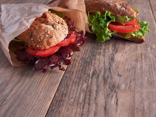 木製のテーブルで隔離の紙袋に野菜のバゲット