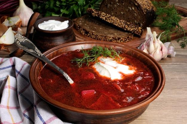 Овощной свекольный суп на столе с кусочками ржаного хлеба и глютеном сметаны