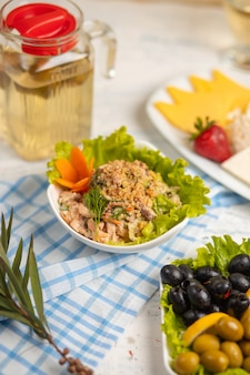 Vegetable, bell pepper, chicken salad with dip sauce served with olives