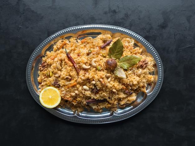 Овощное бирьяни, вегетарианское блюдо на черном столе. вид сверху