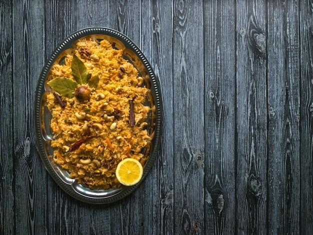 野菜ビリヤニ、黒いテーブルの上のベジタリアン料理。上面図