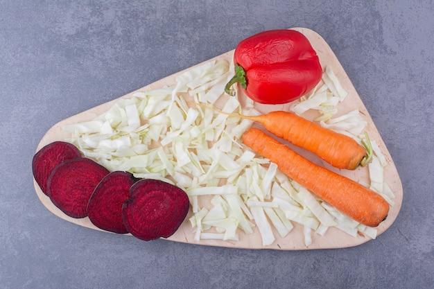Tagliere di verdure con carote, cavoli, barbabietole e peperoncino.
