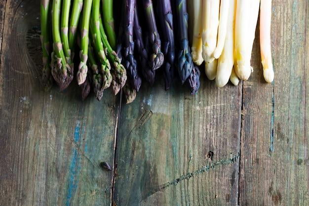 木製の背景に新鮮な天然有機アスパラガスの槍から野菜枠。上面図。