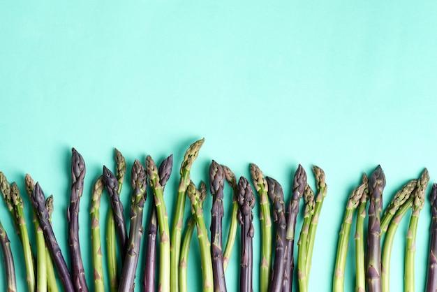 青色の背景に自家製ダイエット食品を調理するための新鮮な天然生アスパラガスの槍からの野菜の境界線。