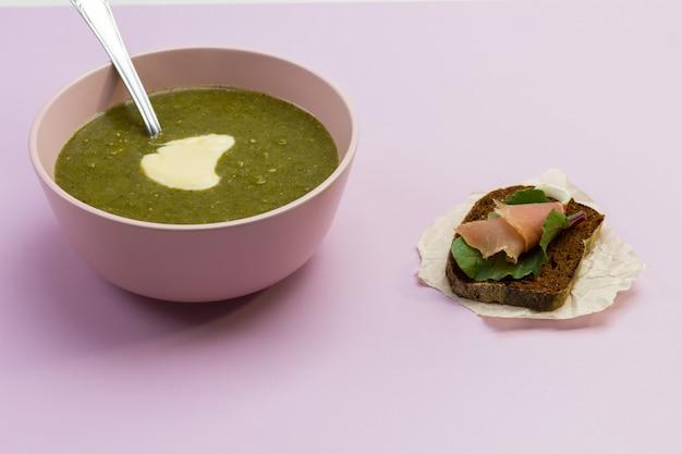 ピンクのボウルに野菜のブロッコリーのピューレスープと机の上のサンドイッチ。