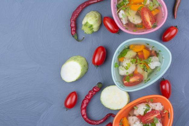 파랑에 다채로운 컵에 야채 국물 수프.