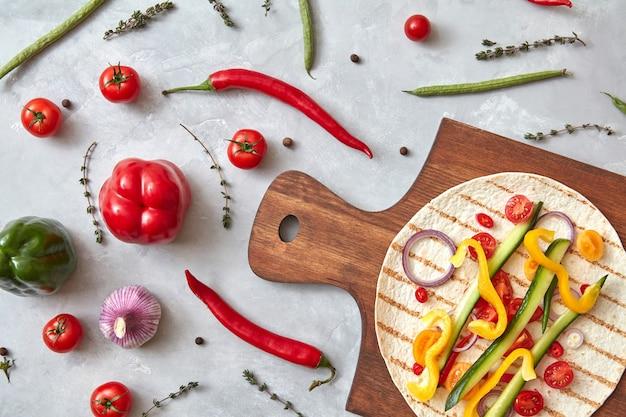 皿と木の板に野菜のブリトー