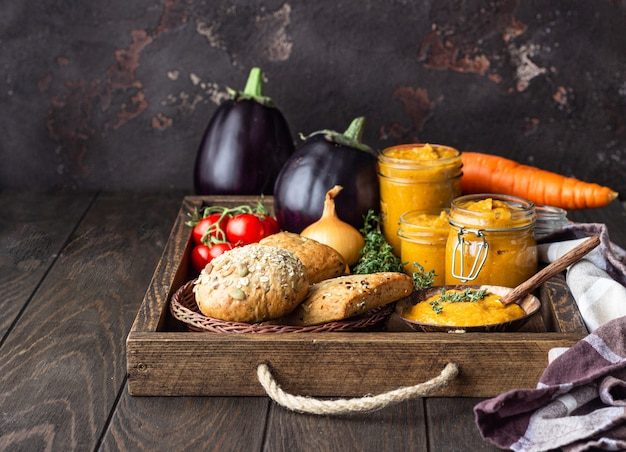 Vegetable caviar in jars, fresh tomatoes, onion, carrot, eggplants and thyme served with bread in a wooden tray.