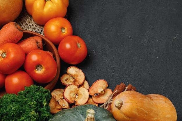 黒の背景の上面図にカボチャ、トマト、乾燥リンゴと野菜の組成物