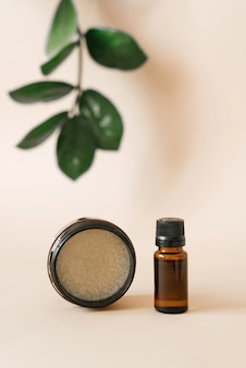 ビューティーサロンでのボディケアのための野菜化粧品。瓶と緑のザミオクルカの葉とベージュ色の背景に油が付いている瓶