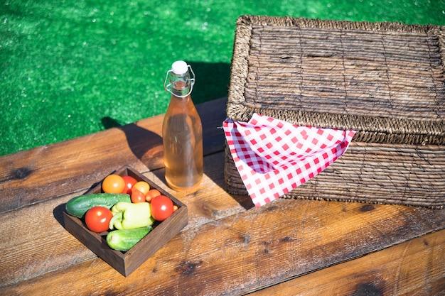 野菜クレート;オリーブオイルボトル、ピクニックバスケット、木製テーブル