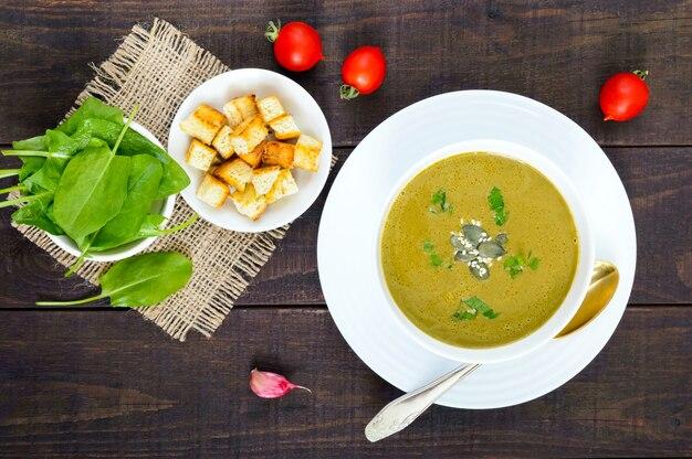 Овощной крем-суп со шпинатом и картофелем в белой миске с чесночными гренками на темном деревянном столе