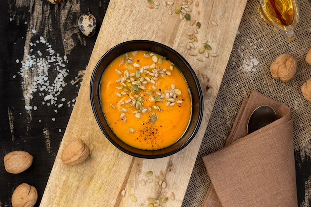 Vegetable dish pumpkin soup with seeds on a wooden cutting board, top view