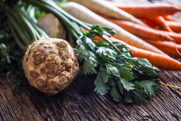 野菜。素朴なオークのテーブルに新鮮な根菜のセロリにんじんとパースニップ。